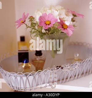 Flower arrangement and perfume bottles on metalwork tray - Stock Photo
