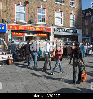 General street view of Wentworth Street part of Petticoat Lane Market includes pavement clothing rails and traders - Stock Photo