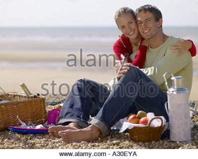 Couple having a picnic on a beach - Stock Photo