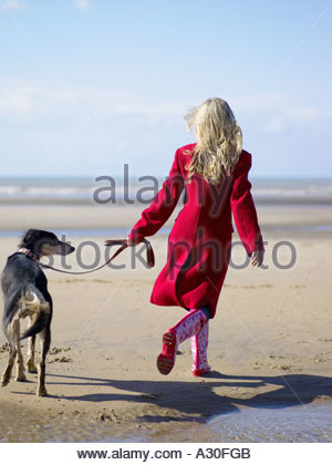 Woman walking her dog on the beach - Stock Photo