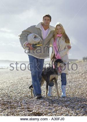 Couple on beach with their dog - Stock Photo