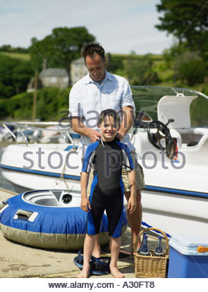 Father dressing son in wet suit - Stock Photo