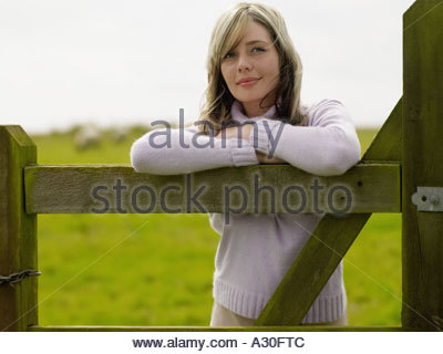 Young woman leaning on wooden gate - Stock Photo