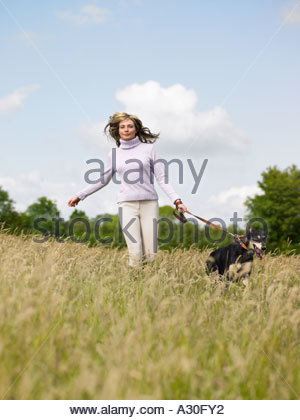 Young woman running through field with dog - Stock Photo