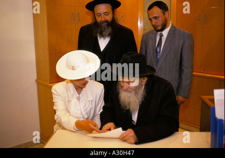 The bride signs her marriage certificate in the presence of her husband and two Rabbi's, Jerusalem Israel - Stock Photo