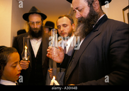An Orthodox Jewish Rabbi lighting candles with a boy at a Jewish Wedding in Jerusalem, Israel - Stock Photo