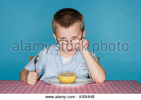 Sullen boy with a grapefruit - Stock Photo