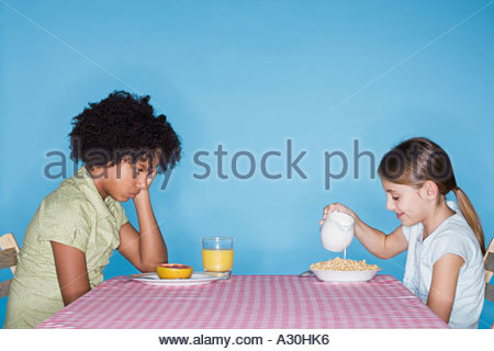 Sullen girl looking at friend's breakfast - Stock Photo