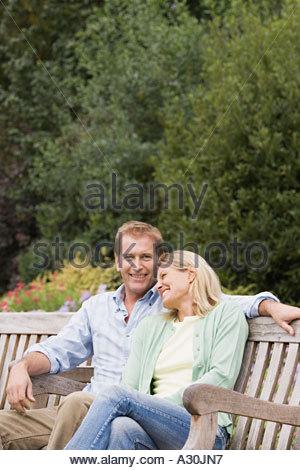 Couple sitting on bench - Stock Photo