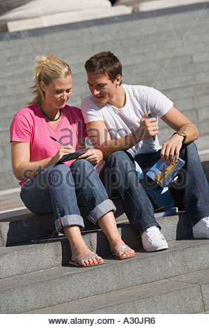 Couple writing postcards on steps - Stock Photo