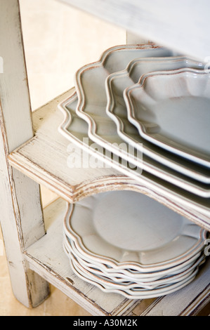 Stack of plates and serving bowls on worn painted shelving - Stock Photo