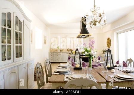 Kitchen with Chandelier above double table with place settings ready to eat - Stock Photo