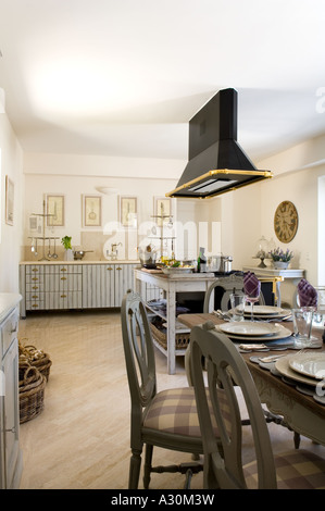Open plan kitchen diner with checked patterned chairs at table setting - Stock Photo