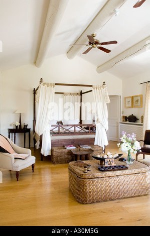 Bedroom with wicker storage chest, four poster bed and ceiling fan - Stock Photo