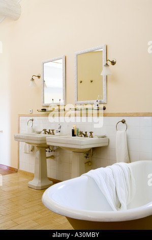 Double washbasins in bathroom with freestanding bath - Stock Photo