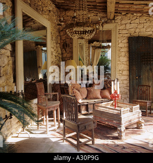 Wooden table and chairs and exposed stone interior in Provençal house - Stock Photo