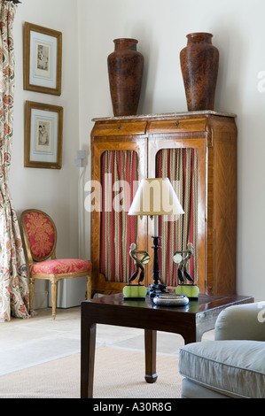 Lamp on side table with wardrobe and urns - Stock Photo
