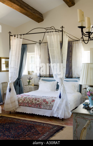 Fourposter bed in bedroom with beamed ceiling in a traditional Provençal house - Stock Photo