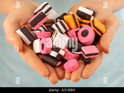 WOMAN HOLDING LICORICE ALLSORTS SWEETS / CANDIES - Stock Photo