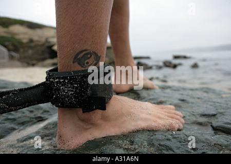 Safety strap on surfer's leg - Stock Photo