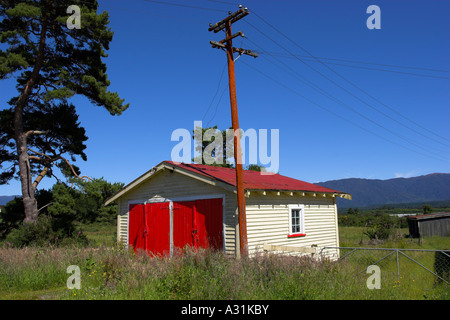 Old garage with red doors. Ahaura Culvert, South Island, New Zealand. - Stock Photo