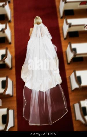 Bride walking down church aisle - Stock Photo