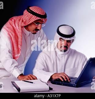 Two Saudi men around laptop - Stock Photo
