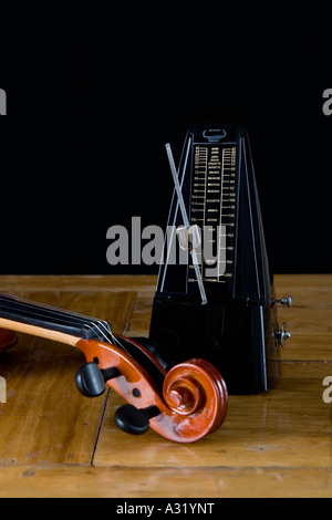 Metronome and violin on wooden table - Stock Photo