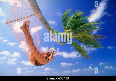 Woman lying in hammock under palm tree Maldive Islands - Stock Photo