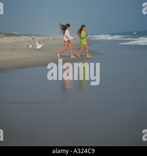 Two young girls walking along the shore in the direction of the water - Stock Photo