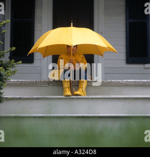 Child wearing rain boots a rain coat and holding an umbrella while sitting on the patio steps in the rain - Stock Photo