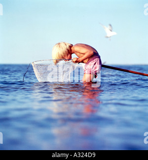 Young boy standing in shallow ocean water hunched over and looking into a fishing net - Stock Photo