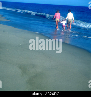 Father mother and daughter holding hands as they walk along the seashore on a sunny day - Stock Photo
