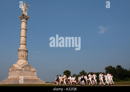 A drum and fife corps marching in front of the Battle of Yorktown monument in Yorktown Virginia - Stock Photo