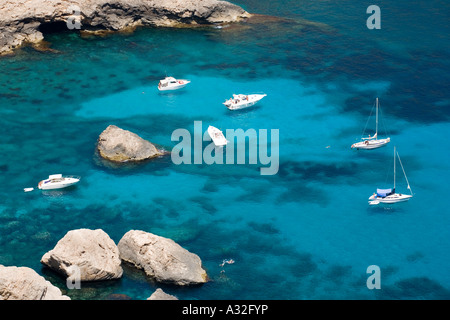 Holidaymakers anchor their boats in the blue sea at Cala Figuera in Mallorca - Stock Photo