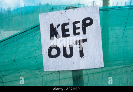 Rough handpainted sign stating Keep out in front of green nylon netting and wire and sheep fencing on sand dunes - Stock Photo