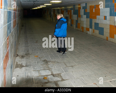 MR woman walking alone in the night through an empty pedestrian underpass underground crossing looking back anxiously - Stock Photo