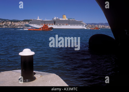 P O Line cruise liner Arcadia plus passing tugs viewed from under the bow of a RoRo cargo ferry in the Port of Palma - Stock Photo