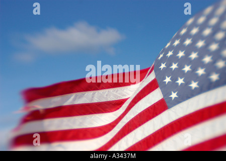 The American Flag waves against a blue sky - Stock Photo
