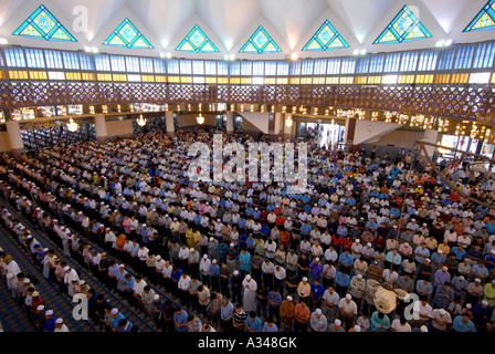 Muslim men at Friday prayer in the National Mosque, Kuala Lumpur, Malaysia - Stock Photo