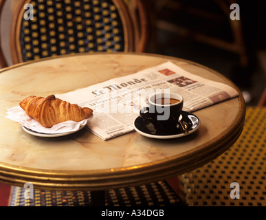 Coffee, croissant and newpaper in cafe , Paris, France . - Stock Photo