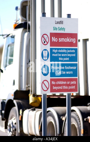 Royalty free photograph of lorry arriving at UK landfill site in London with warning signs at site - Stock Photo