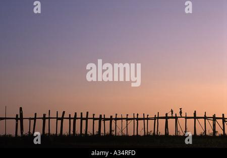Villagers crossing the U Beins bridge at sunset Amarapura Myanmar - Stock Photo