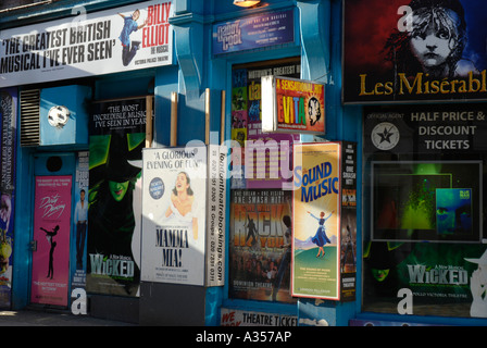 Colourful posters advertising shows outside West End theatre ticket agency London England - Stock Photo