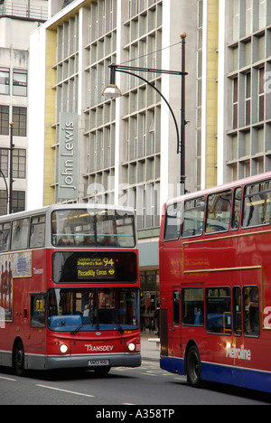 View of Oxford Street showing John Lewis department store and two red buses London - Stock Photo