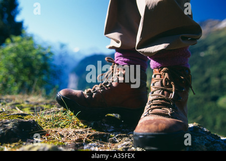 hiking boots with mountain landscape Bernese Oberland Switzerland - Stock Photo