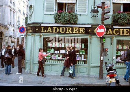 Paris France, Tourist Couple, Woman Taking pictures on Street  Outside Old Vintage French Bakery Shop, Laduree, - Stock Photo