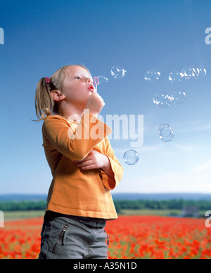 Young girl blowing bubbles in a field of poppies - Stock Photo