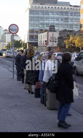 orderly line queue of people in a taxi rank standing on the footpath by the side of a road - Stock Photo