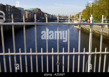 looking down the liffey through railings on the hapenny ha penny bridge over the river liffey in dublin - Stock Photo